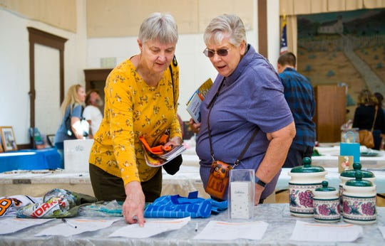 Cindy Linda, left, and Jackie Collins, from Dayton, examine some of the items available at the silent auction.