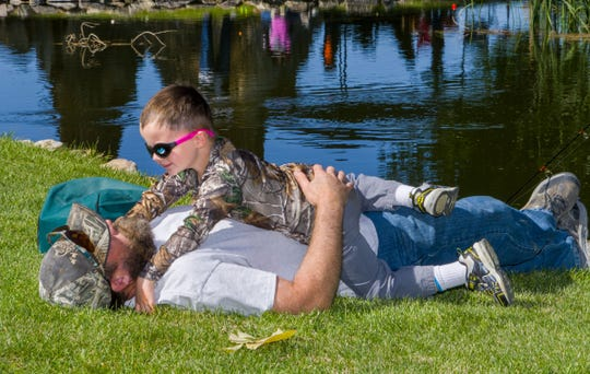 Levi House, 3, wrestles with his dad, Jeff House of Dayton, as they wait for fish to bite during fishing derby.