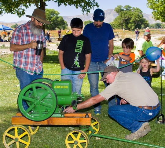 Ken Wellnitz, a park aide, demonstrates one of two John Deere motors he built several years ago to church ice cream.