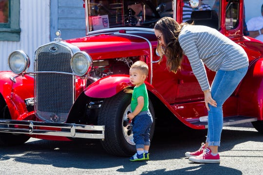 A young boy checks out a car on display at the car show.
