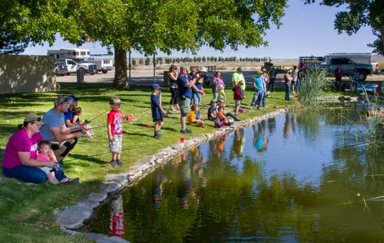 Children and adults participate in a kids' fishing derby at the Walker River Recreation Area. The Nevada Department of Wildlife stocked the pond with more than 200 fish.
