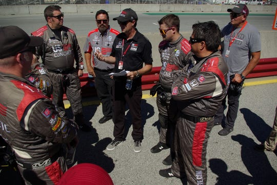 Bryan Herta, whose son Colton Herta won Firestone Grand Prix of Monterey Sept. 22, 2019, leads a pre-race meeting of crew members for third-generation driver Marco Andretti of Andretti Autosport. Herta coaches Andretti. A two-time winner at Laguna Seca, the elder Herta also coached the winning driver for the 2010 (Dan Wheldon) and 2016 (Alexander Rossi) Indianapolis 500s.