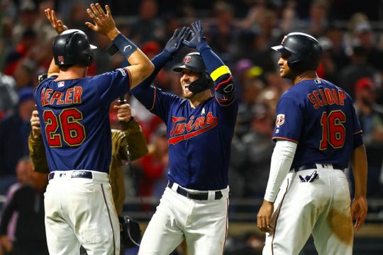 Max Kepler (L), Mitch Garver and Jonathan Schoop (R) celebrate a home run during a game in Cleveland during the 2019 season.