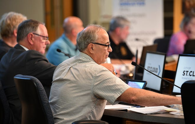 City council member George Hontos takes his seat for a city council meeting in July.