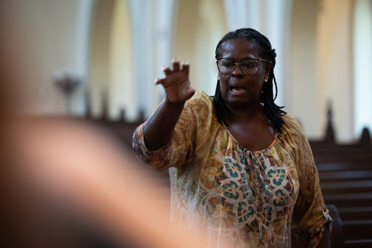 Patrice Floyd, founder of the Javacya Elite Chamber Orchestra, leads the group in a warm up at St. Peter's Anglican Cathedral at a Sunday rehearsal.