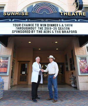 Dr. Ron Lyman, left, and Mike Adams in front of the Sunrise Theatre marquee promoting the chance to win dinner and show tickets.