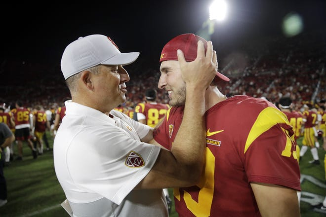 USC head coach Clay Helton, left, congratulates quarterback Matt Fink after the team's 30-23 win over Utah last Friday night.