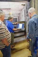 Max Brown, Gale Cochran-Smith and Wes Morton look at the digital photo album that will be installed in one of the rooms of the frontier town at the Tales 'N' Trails Museum in Nocona, Texas.