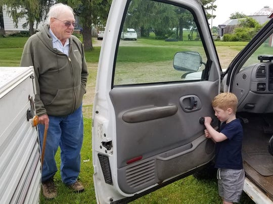 Grandson Harrison is fascinated by the manual window crank inside Grandpa Bob's old farm truck.