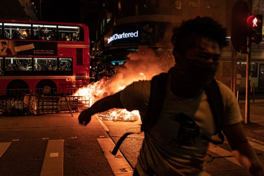 A pro-democracy protester runs away from a burning barricade outside of the Mongkok Police Station as a bus drives in front of it on September 22, 2019 in Hong Kong, China.