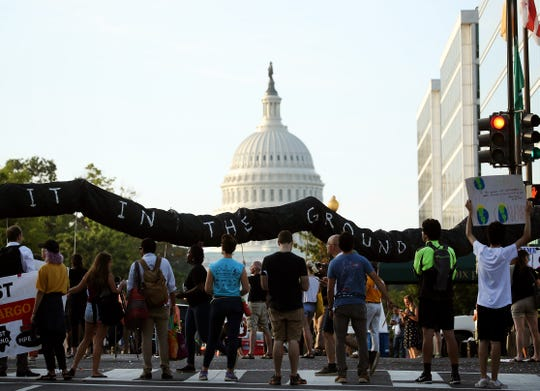 Climate change protesters block traffic on Massachusetts Ave. during a protest to shut down D.C. on September 23, 2019 in Washington, DC. The protesters are urging for climate action and want the reallocation of the budget away from the military to fund a Green New Deal.
