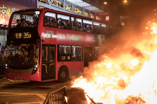 Passengers look out from a bus at a  burning barricade lit by pro-democracy protesters during a protest gathering in front of Mong Kok police station on September 22, 2019 in Hong Kong, China.