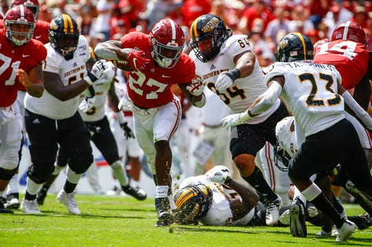 Alabama running back Jerome Ford carries the ball as Southern Miss  defensive lineman Ethan Edmondson (84) tries to tackle him.