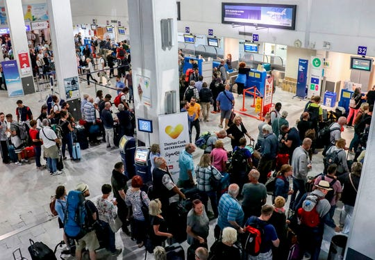 Tourists wait at a Thomas Cook company counter at Heraklion airport on the island of Crete on September 23, 2019. British travel group Thomas Cook declared bankruptcy on September 23, 2019, after failing to reach a last-ditch rescue deal, triggering the UK's biggest repatriation since World War II to bring back stranded passengers. The 178-year-old operator had been desperately seeking £200 million ($250 million, 227 million euros) from private investors to save it from collapse.
