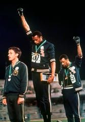 Tommie Smith, center, and John Carlos, right, extend gloved hands skyward in protest in an iconic image from the 1968 Olympics in Mexico City.