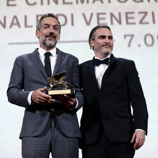 """Todd Phillips, left, and Joaquin Phoenix receive the Golden Lion Award for Best Film  for """"Joker"""" during the award ceremony during the 76th Venice Film Festival at Sala Grande on Sept. 7, 2019 in Venice, Italy."""