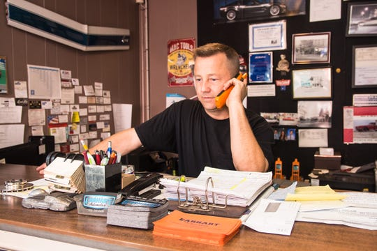 Owner Jared Earhart answering phone calls and doing administrative work at Earhart Automotive in Freehold. Sept. 24, 2019
