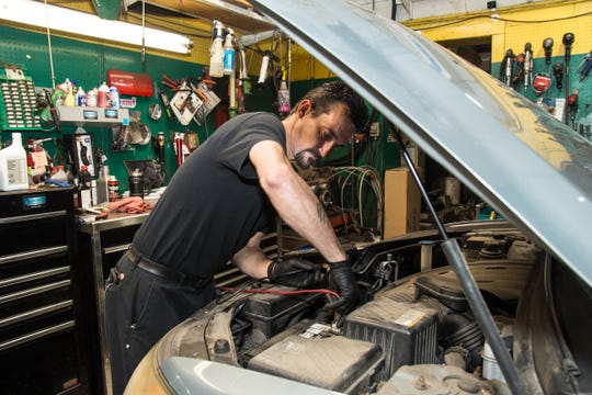 Mechanic John Maze of Earhart Automotive in Freehold checking the charge of a battery. Sept. 24, 2019
