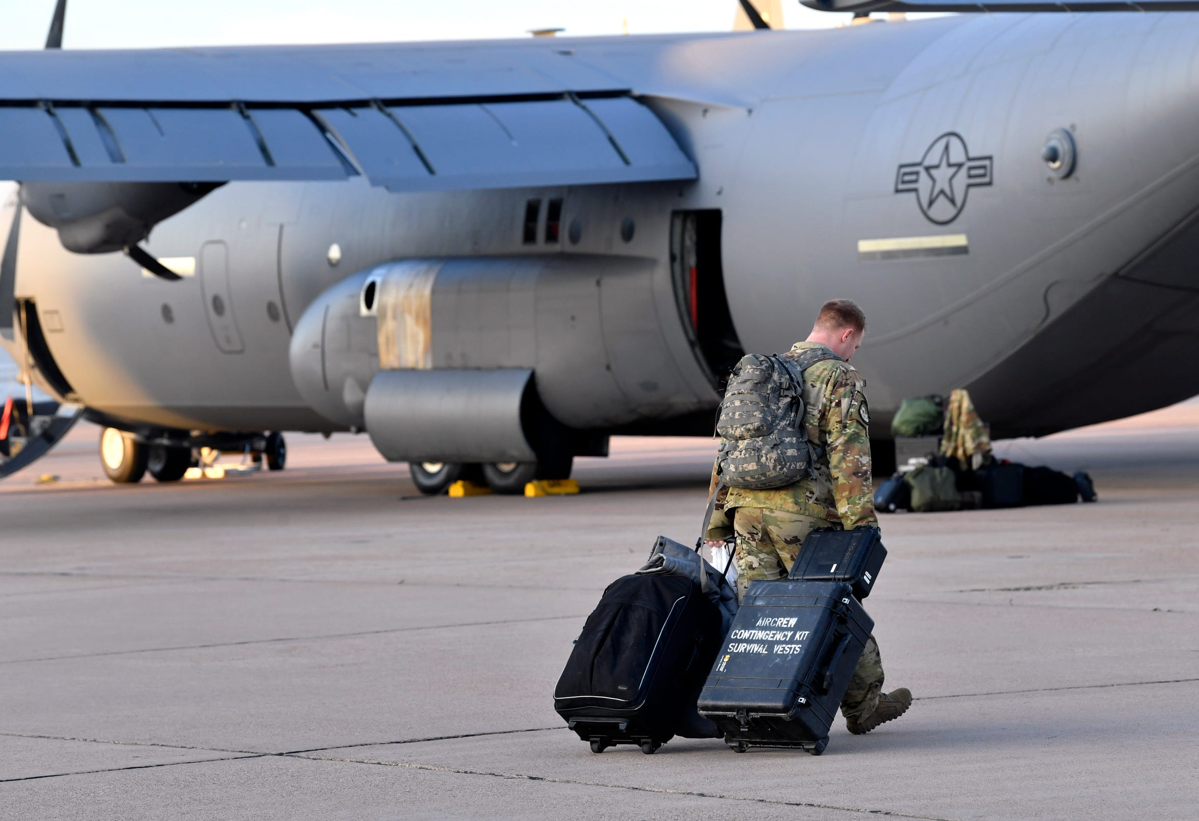 An airman wheels his luggage onto the flight line at Dyess Air Force Base on Sept. 9. Members of the 39th Airlift Squadron packed not only for their four-month deployment to Afghanistan, but for the three or more days it would take to fly there in their C-130J Super Hercules cargo planes.