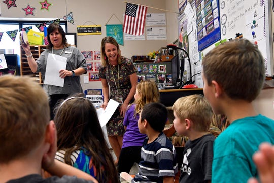 Jessica Melson with the Abilene Education Foundation, shakes a tambourine as first-grade teacher Amanda Martin celebrates with her class being awarded a $994 grant Tuesday during the Prize Parade.