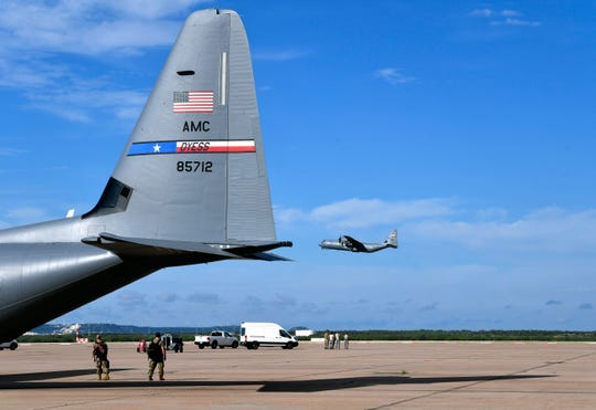 Airmen watch a 39th Airlift Squadron C-130J Super Hercules take off at Dyess Air Force Base Sept. 9. It joined other aircraft already aloft in the largest deployment of the squadron in more than a decade.