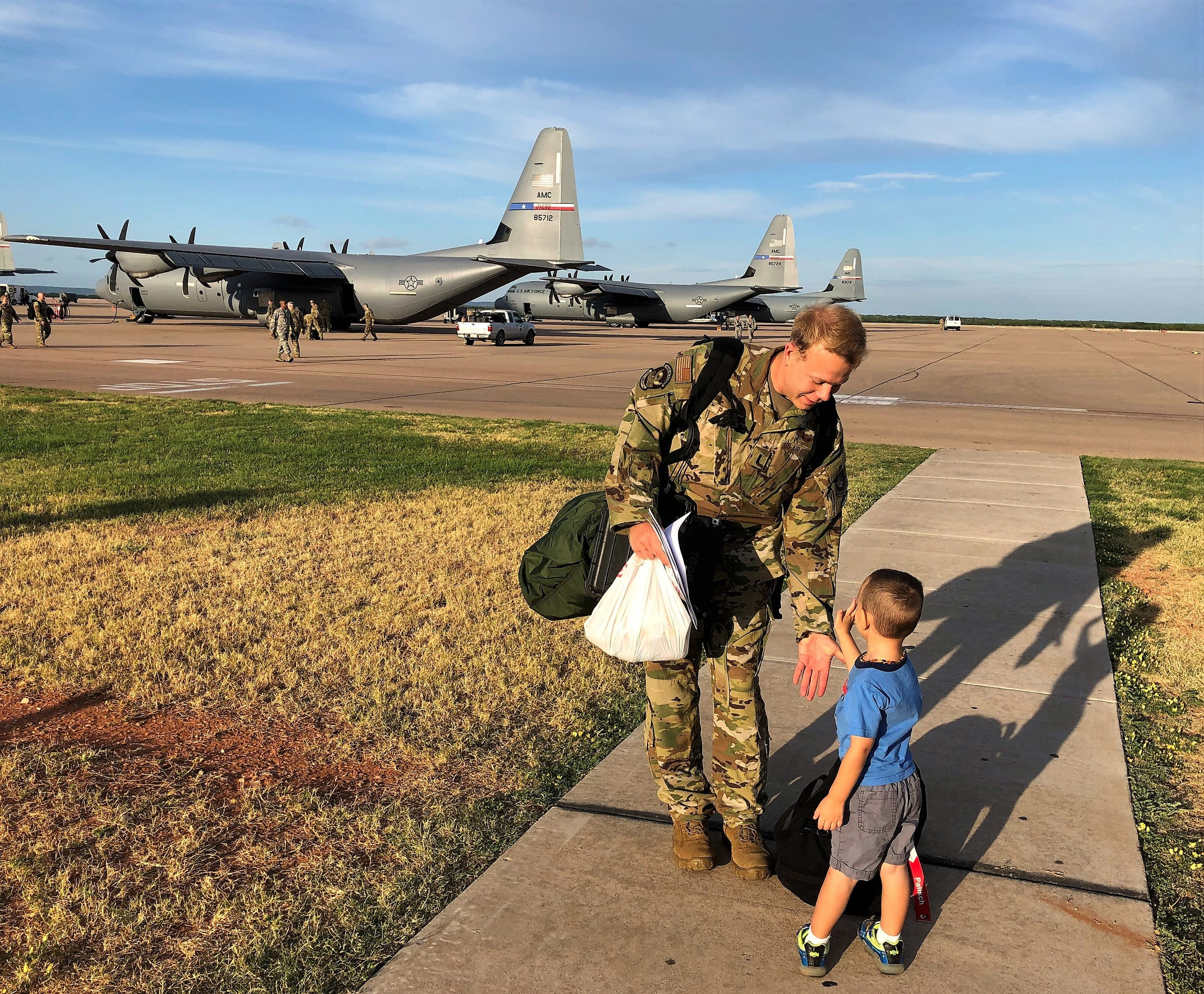 A Dyess Air Force Base airman headed toward his plane drops his bag to accept a high-five from Gregory Fearing, 3, near the edge of the tarmac Sept. 9. The youngster was on duty to wish good luck to airman about to deploy.