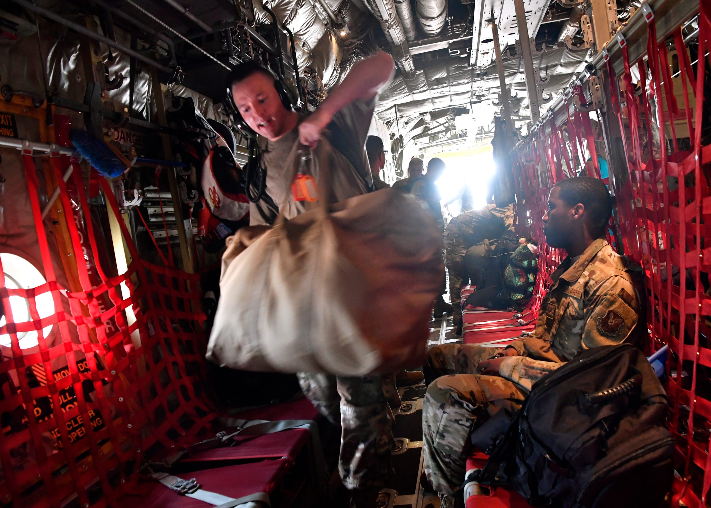 Senior Airman Michael Thornton squeezes past Staff Sgt. Carter Thompson as their C-130J Super Hercules is readied for flight at Dyess Air Force Base.