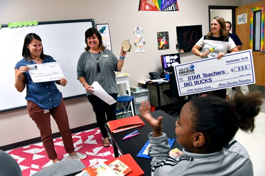 Bonham Elementary School special education teacher Lindsey Owen holds up her grant check Tuesday given to her by the Abilene Education Foundation's Prize Parade.