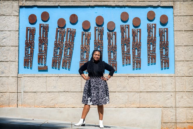 """Cleaster Cotton, who describes herself as a contemporary primitive artist, stands with her mural """"Going to Market"""" on Sept. 24, 2019. The mural is located on a new condominium project on South Market Street at the gateway to """"The Block,"""" the city's historic African American business district. Cotton also has a new exhibit of paintings on display at Pink Dog Creative in the River Arts District."""