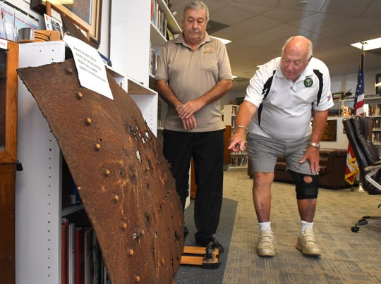 Don Pearsall (left), chairman of the Brevard Veterans Council, and Donn Weaver, Brevard Veterans Council special projects officer, examine the piece of the USS Arizona inside the library at the Brevard Veterans Memorial Center on Merritt Island.