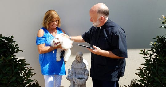 Suntree resident June Mikell holds furry best friend Lucas as Pastor David Jahn of Advent Lutheran Church blesses the pup. Advent will host its annual Blessing of the Animals both in Suntree and Melbourne on Saturday, Oct. 5. Photo---