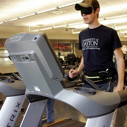 A QL+ student from the University of Dayton tests a treadmill-centering device for a blind veteran.