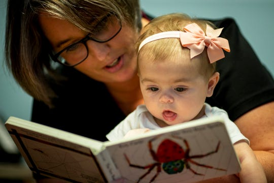 Jill Huff, a speech pathologist, reads with 4-month-old Rosie, during a therapy appointment on Friday, Sept. 20, 2019 at First Step Home in Walnut Hills as part of a Child Resiliency program.