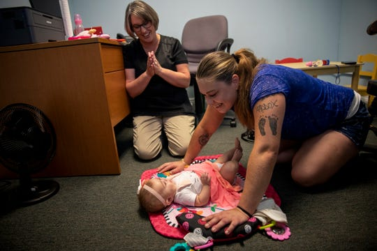 Speech pathologist Jill Huff looks on as Brittany Hill plays with her 4-month-old, Rosie, during their therapy appointment at First Step Home, a treatment center for women with substance-use disorders.