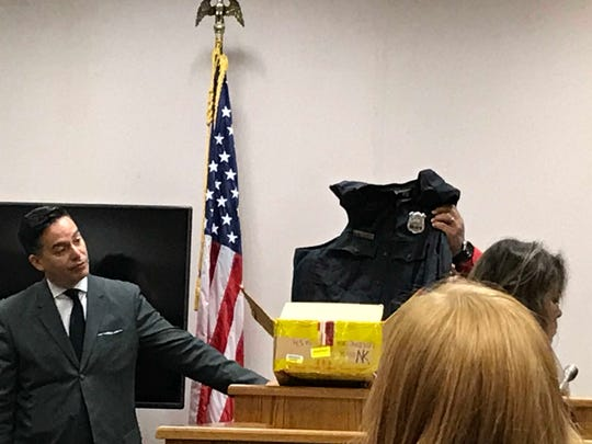 Former Linden Police Officer Angel Padilla holds up his bulletproof vest while questioned by Assistant Prosecutor Albert Cernadas Jr.