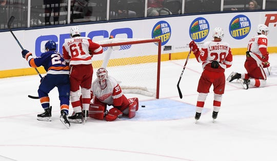 Red Wings goaltender Jimmy Howard and Jacob de la Rose, Gustav Lindstrom and Filip Zadina react after the Islanders' Anders Lee scored an overtime goal during the Wings' 3-2 overtime loss to the Islanders in the preseason game on Monday, Sept. 23, 2019, in Uniondale, N.Y.