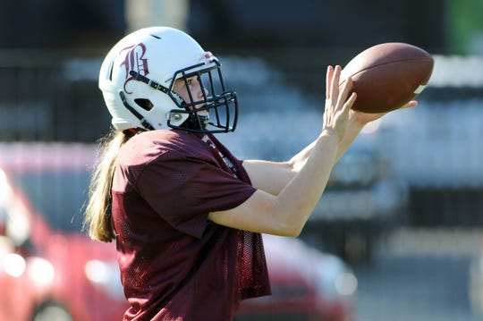 Berkley High School football safety Marcella DePaul catches a football during practice.