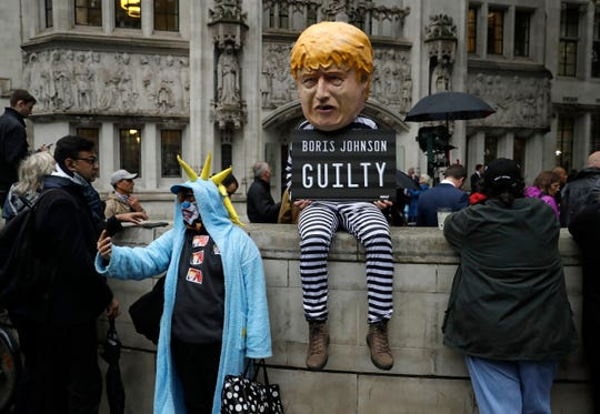 A person dressed as a caricature of British Prime Minister Boris Johnson in a prison uniform stands outside the Supreme Court in London, Tuesday, Sept. 24, 2019 after it made it's decision on the legality of Johnson's five-week suspension of Parliament.