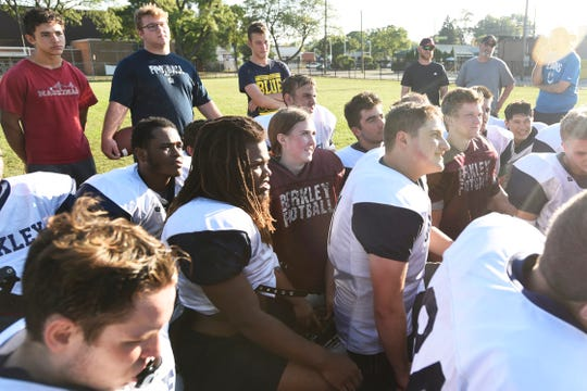 Berkley High School football safety Marcella DePaul, center, listens to head coach Sean Shields address the team at the end of practice.