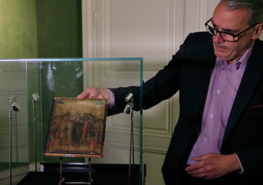 Art expert Stephane Pinta takes out of a class case a 13th century painting by Italian master Cimabue in Paris, Tuesday, Sept. 24, 2019.