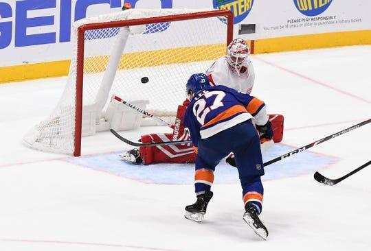 New York Islanders' Anders Lee (27) scores an overtime goal past Detroit Red Wings goaltender Jimmy Howard (35) during Monday's preseason game.
