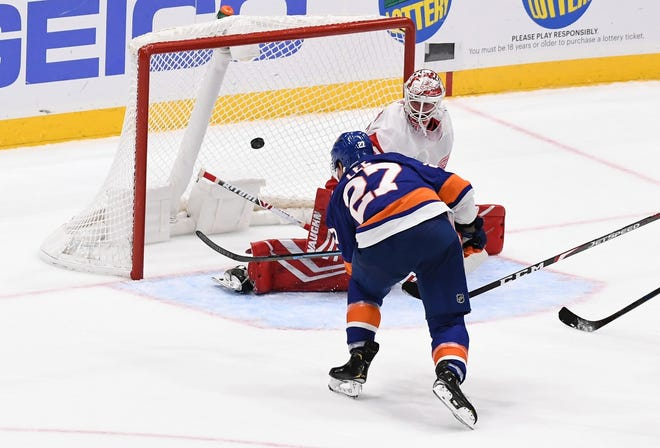 New York Islanders' Anders Lee (27) scores an overtime goal past Detroit Red Wings goaltender Jimmy Howard (35) during Monday's preseason game.
