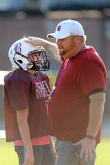 Berkley High School football safety Marcella DePaul, left, gets instructions on where to stand from head coach Sean Shields during practice