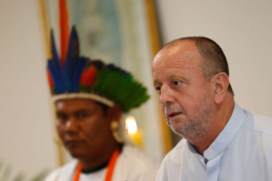 Dom Roque Paloschi, President of the Indigenous Missionary Council, right, speaks next to Surui, a Pataxo Indigenous chieftain, at the launch of the report on violence against indigenous peoples in Brazil, at the headquarters of the National Conference of Bishops in Brasilia, Brazil, Tuesday, Sept. 24, 2019. A Brazilian Catholic Church agency says invasions of indigenous lands have jumped in the first nine months of President Jair Bolsonaro administration.