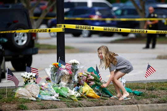FILE - In this Saturday, June 1, 2019, file photo, a girl leaves flowers at a makeshift memorial at the edge of a police cordon in front of a municipal building that was the scene of a shooting, in Virginia Beach, Va. On Tuesday, Sept. 24, 2019, police are expected to release the findings of their investigation into the May 31 fatal mass shooting.