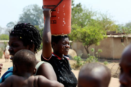 A woman heads home after fetching water at a borehole in Harare, Tuesday, Sept, 24, 2019.