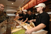Employees prepare food for the lunch crowd at the Chipotle Mexican Grill in West Bloomfield Township.