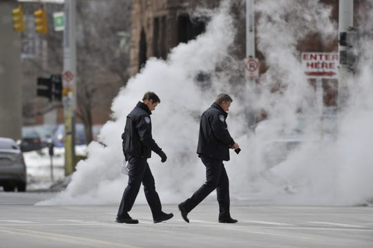 A pair of law enforcement officers walk across Lafayette Boulevard in downtown Detroit as steam billows up from a manhole in the street.