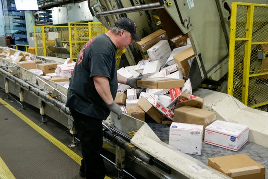 Steve Robino arranges packages on a conveyor belt at the main post office in Omaha, Neb.