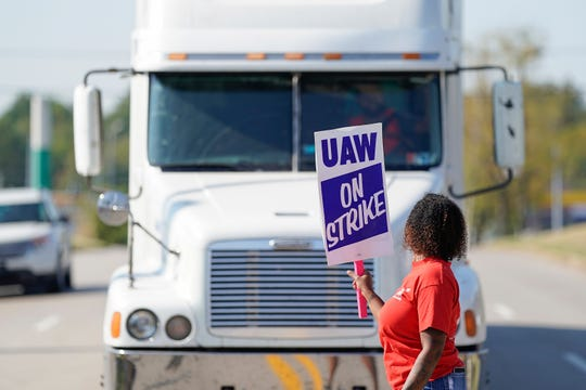 The UAW strike has cost automotive suppliers, trucking companies and other GM affiliates hundreds of thousands in lost revenue as plants, trucks and employees sit idle. Above, a striking plant worker blocks the passage of a truck outside the GM assembly plant in Bowling Green, Ky, Monday.